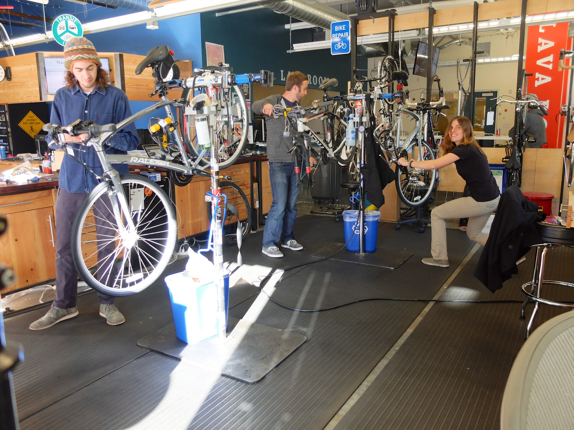 People helping repair bikes.